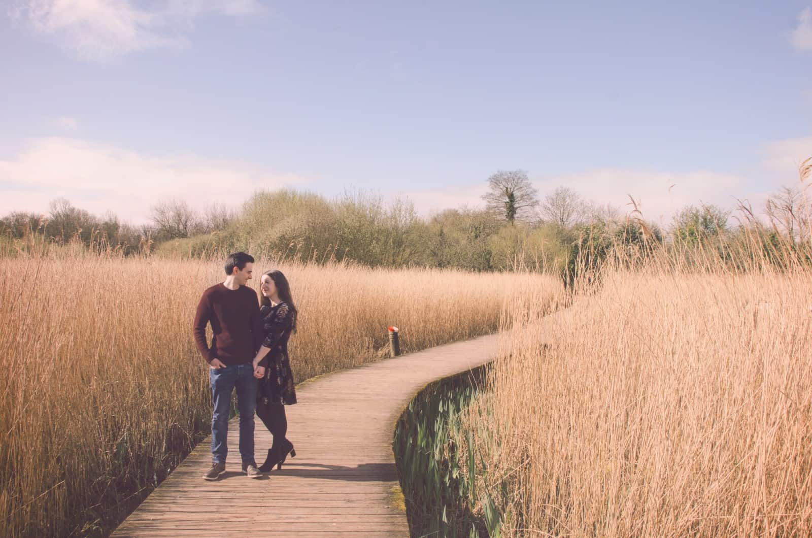 Couple stand on boardwalk hand in hand at Cosmeston lakes