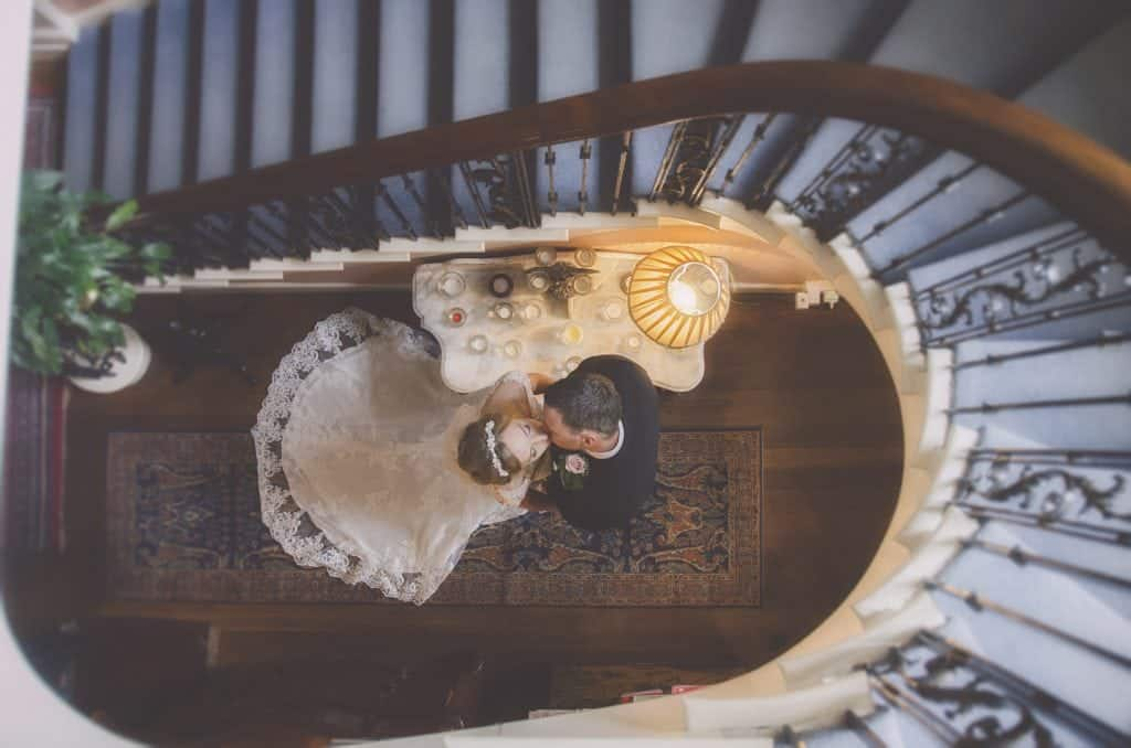 bride and groom kiss in stairwell