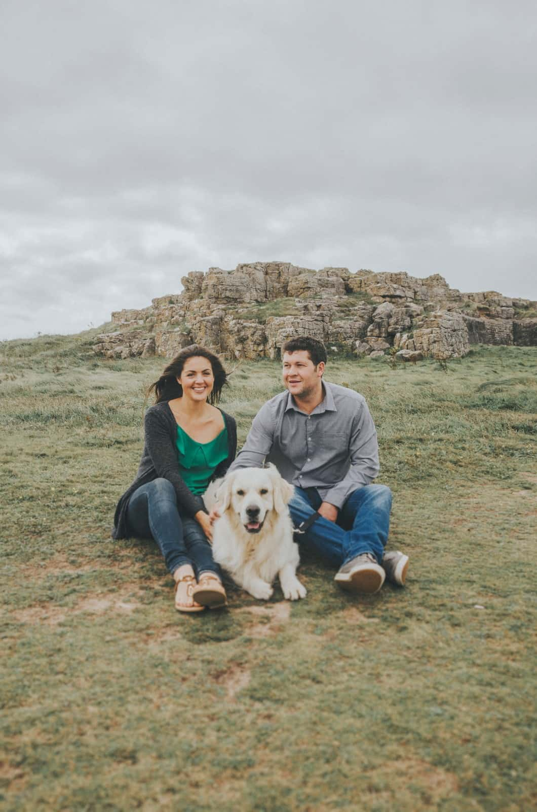 Couple sat on hillside with their dog