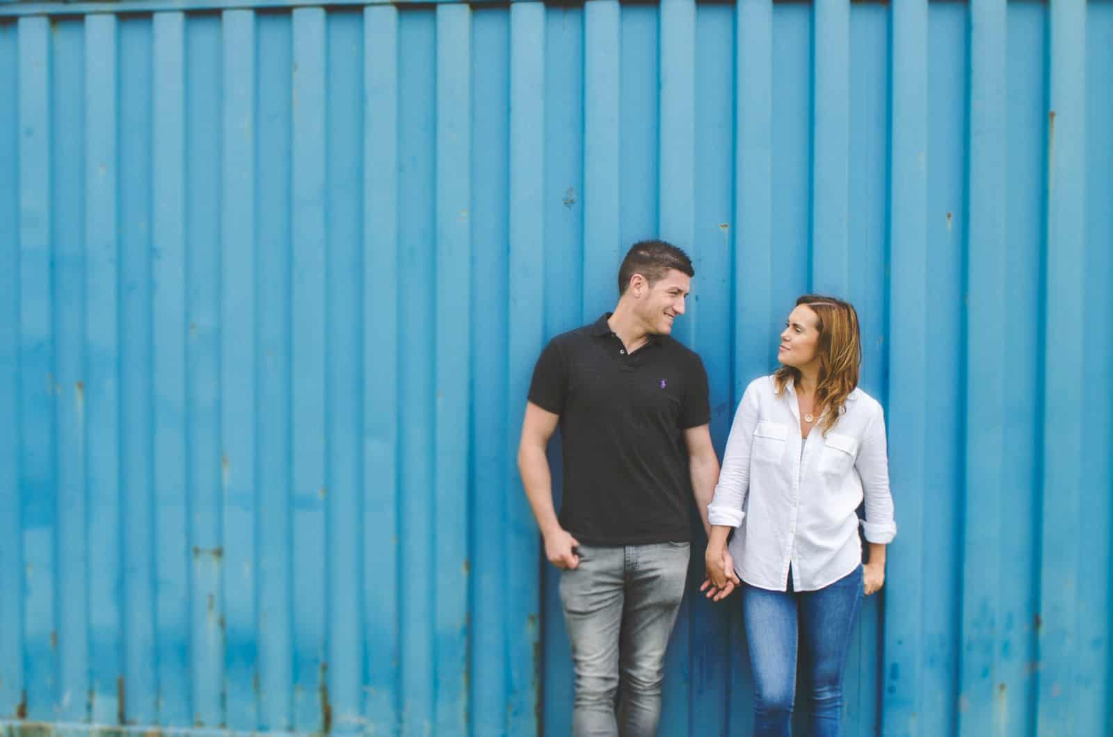 Couple looking at each other standing in front of a blue shipping container