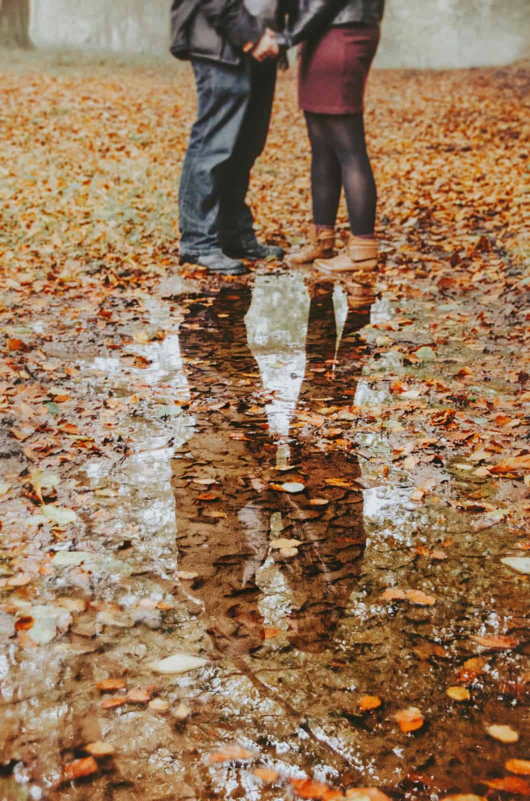 Reflection of couple in woods holding hands in wentwood forest