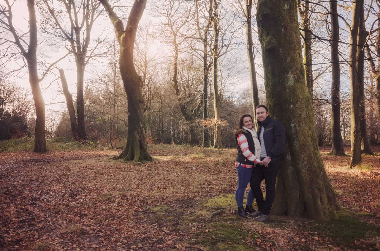 Couple stood against a tree in Wentwood forest