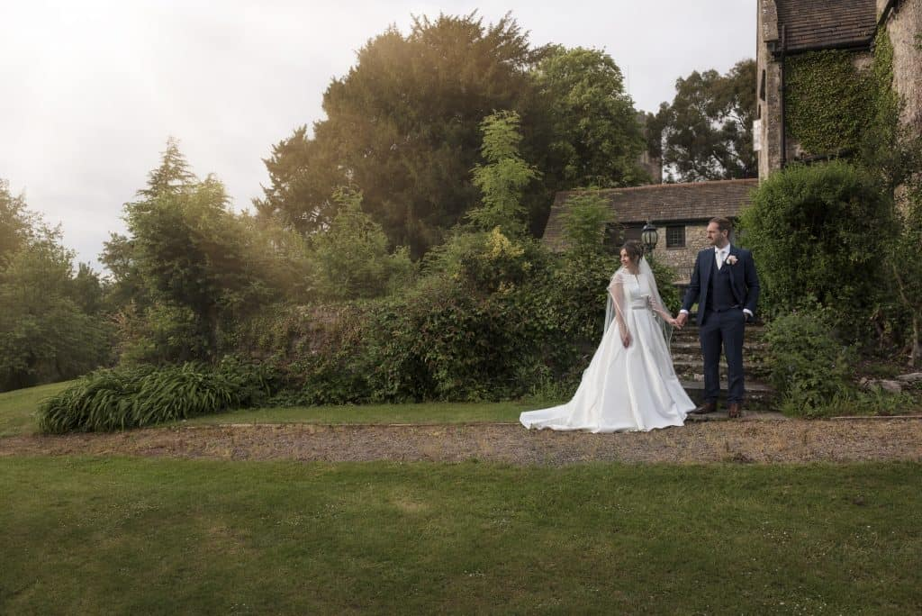 bride and groom stood holding hand in front of old farm buildings