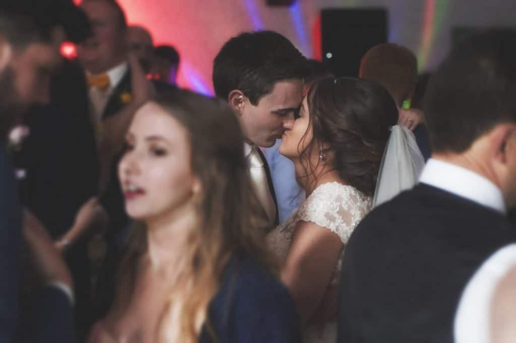 wedding photographers near me Bride & Groom kiss on dance floor surrounded by their guests