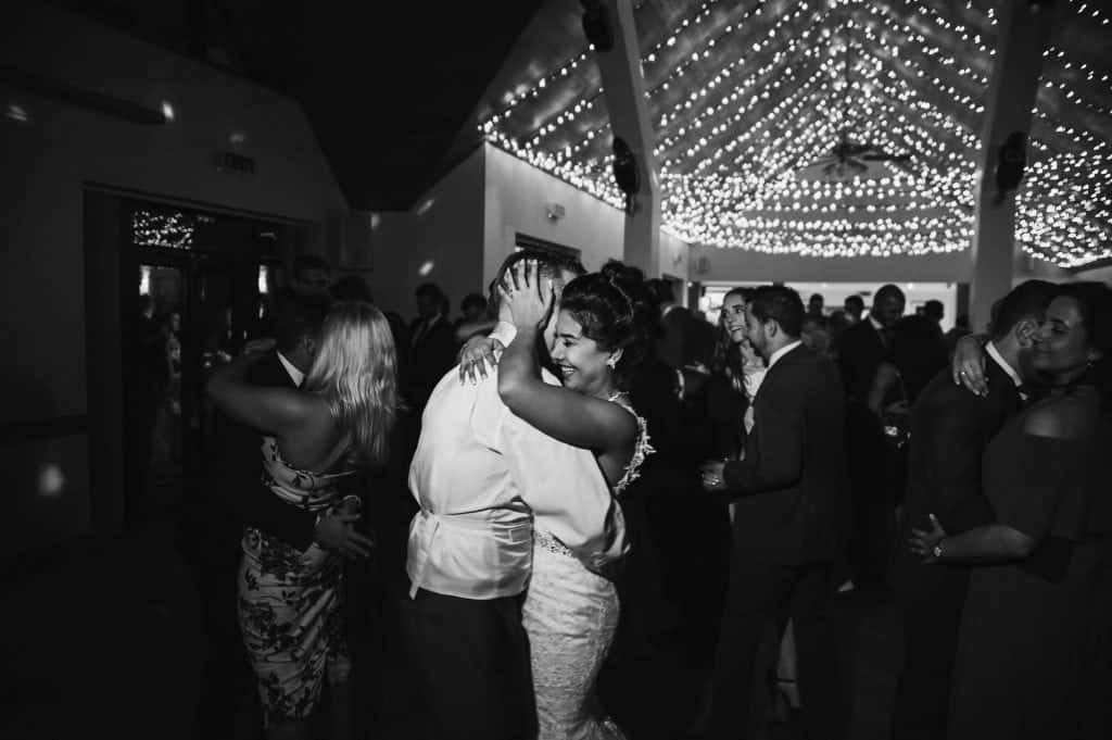 wedding photographers near me - Bride hugs groom whilst dancing in fairy light lit room