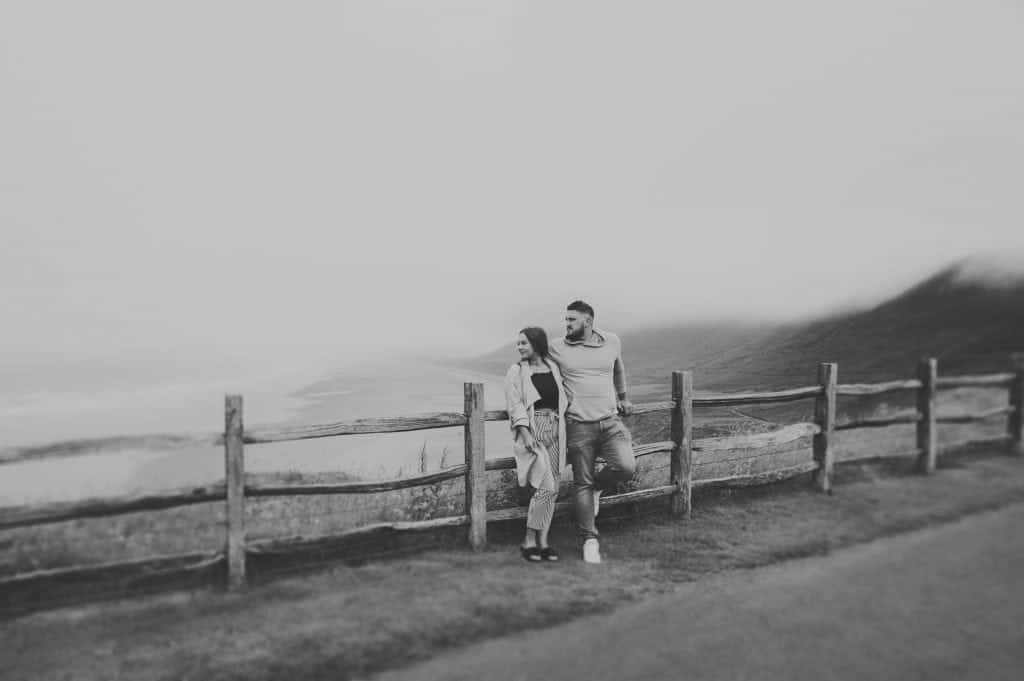 wedding photographers near me a couple stood against a wooden fence looking to the left with a Misty beach behind them