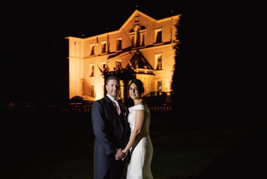 wedding photographers near me Bride and Groom stood at night time in front of a lit up Court Colman Manor, Bridgend
