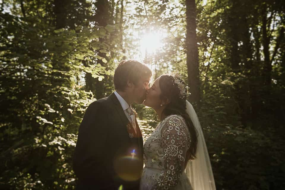 Bride & Groom Kiss in woodland setting with sunlight peaking through trees