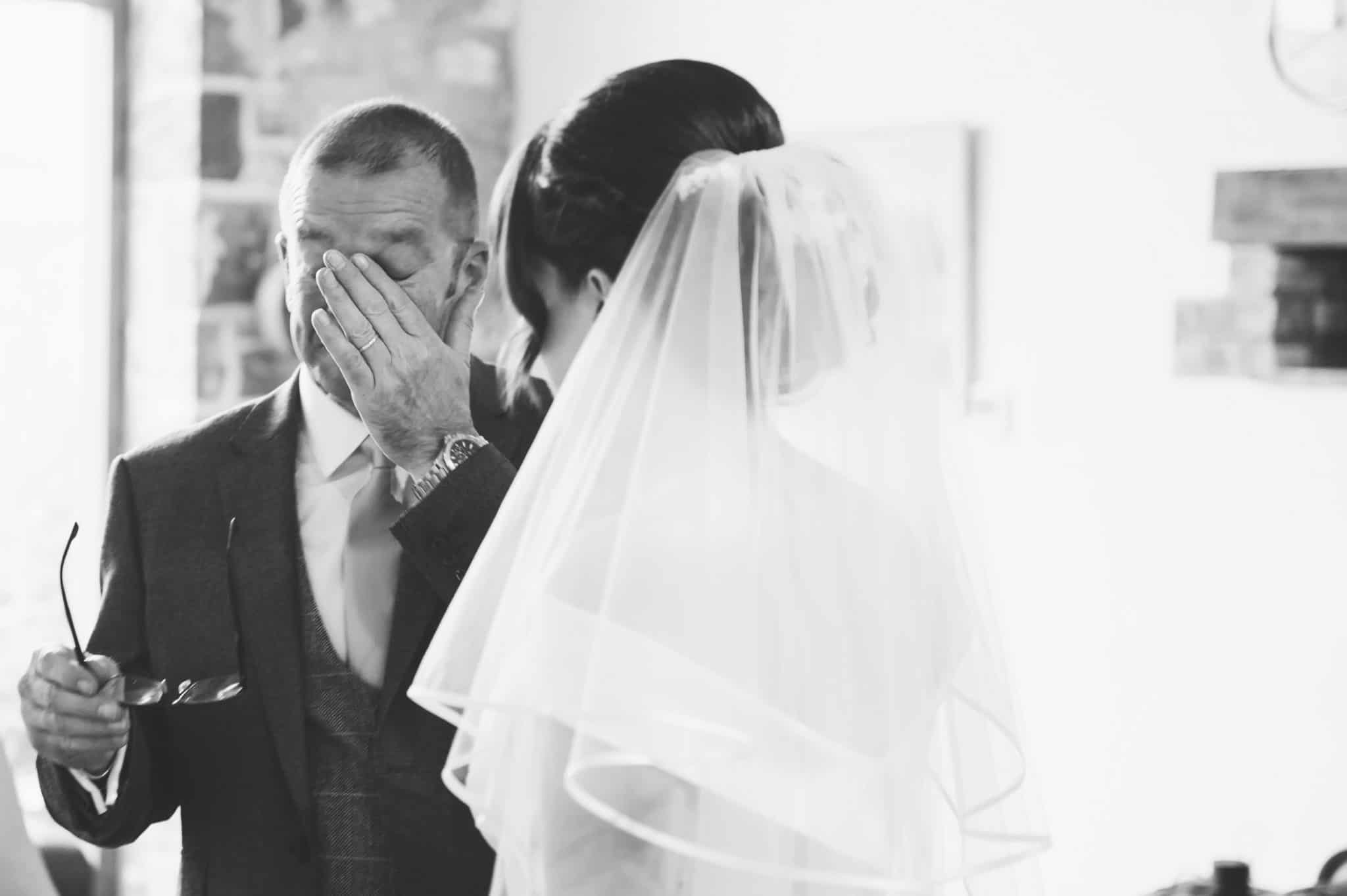 Bride's father wiping away tears