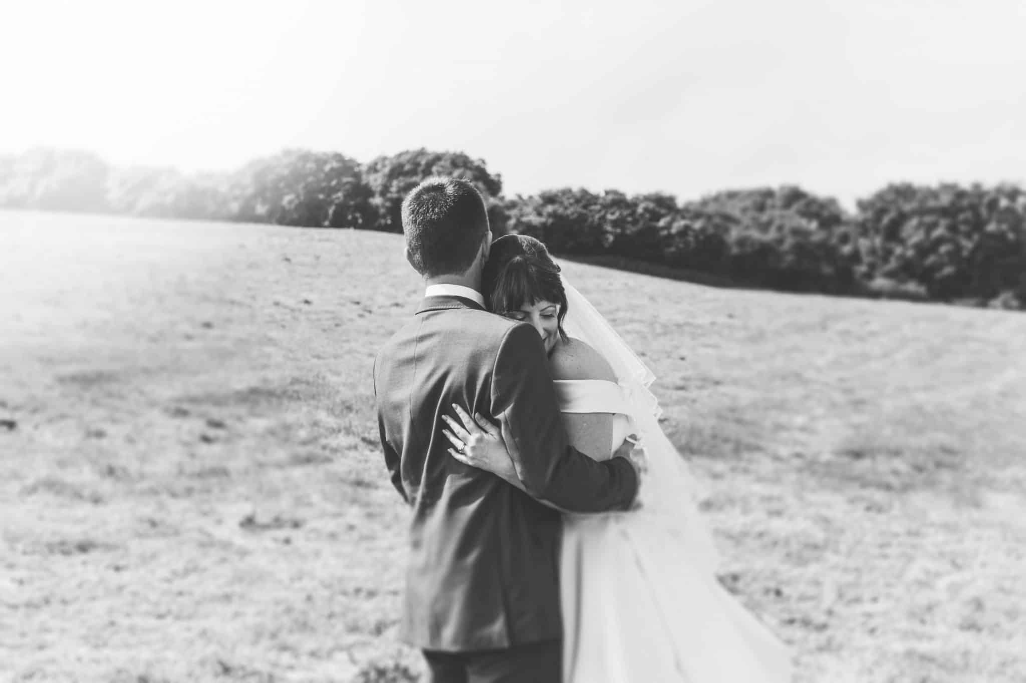 Bride & Groom hug on hillside