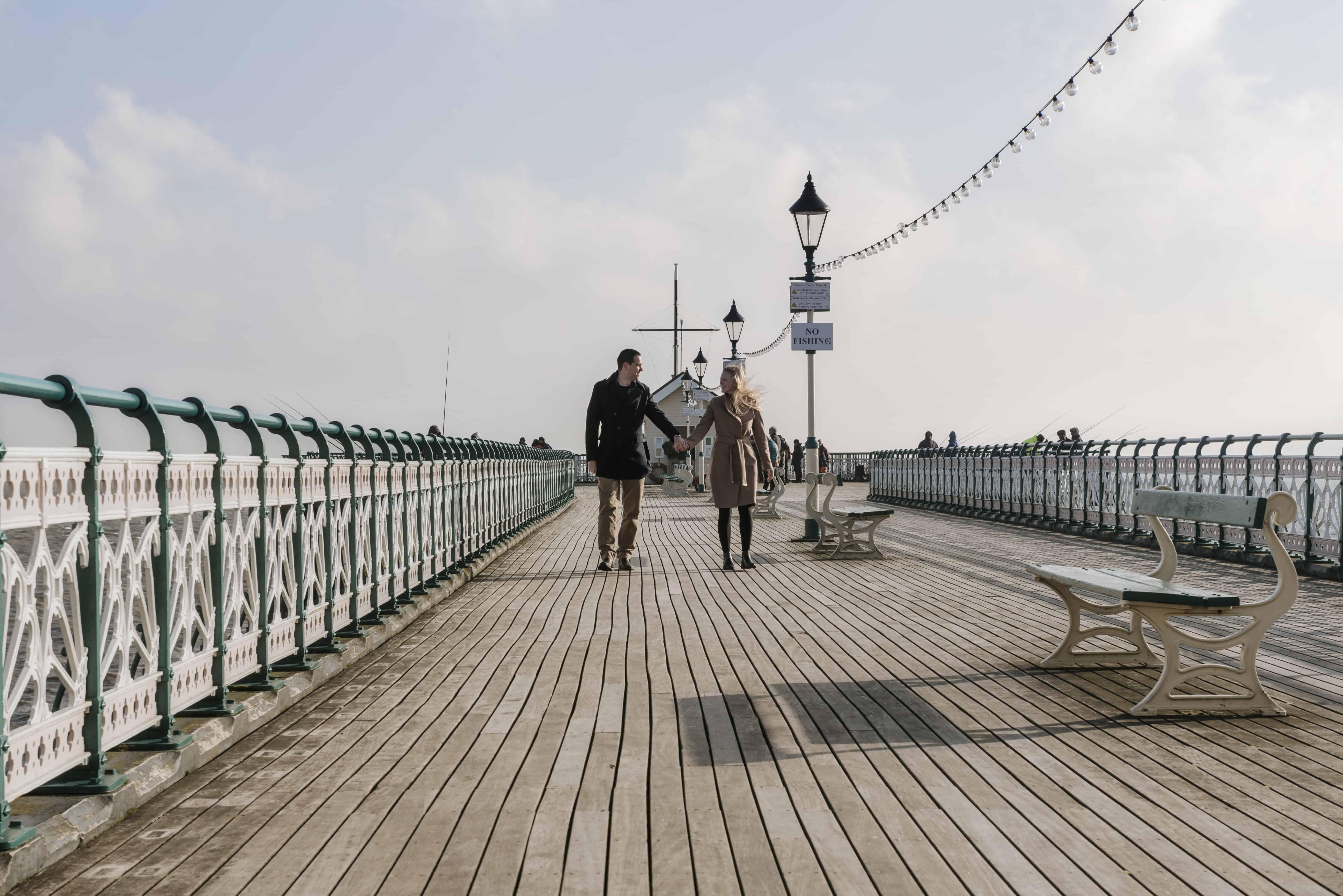 Couple walking down a pier