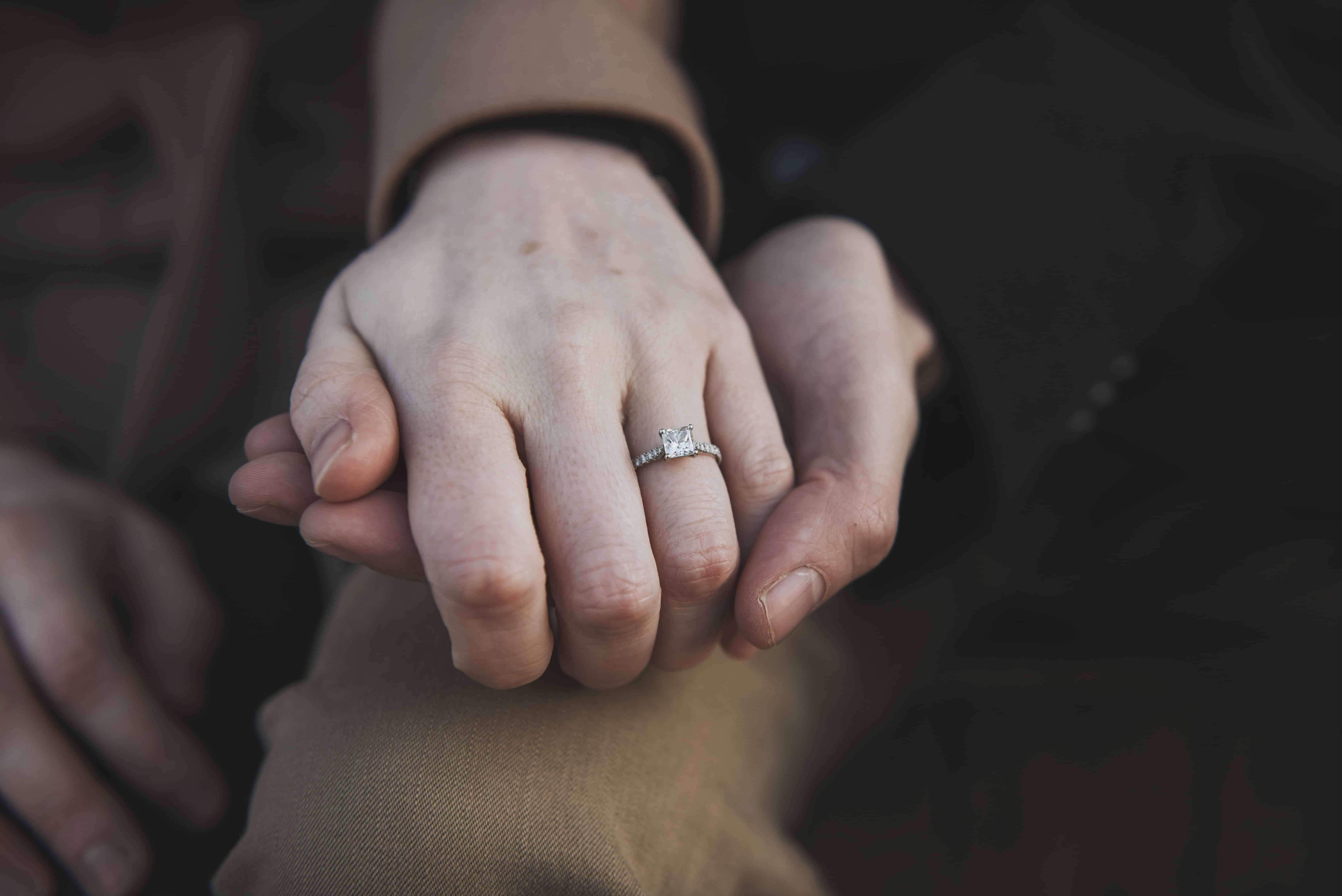Hands holding showing engagement ring