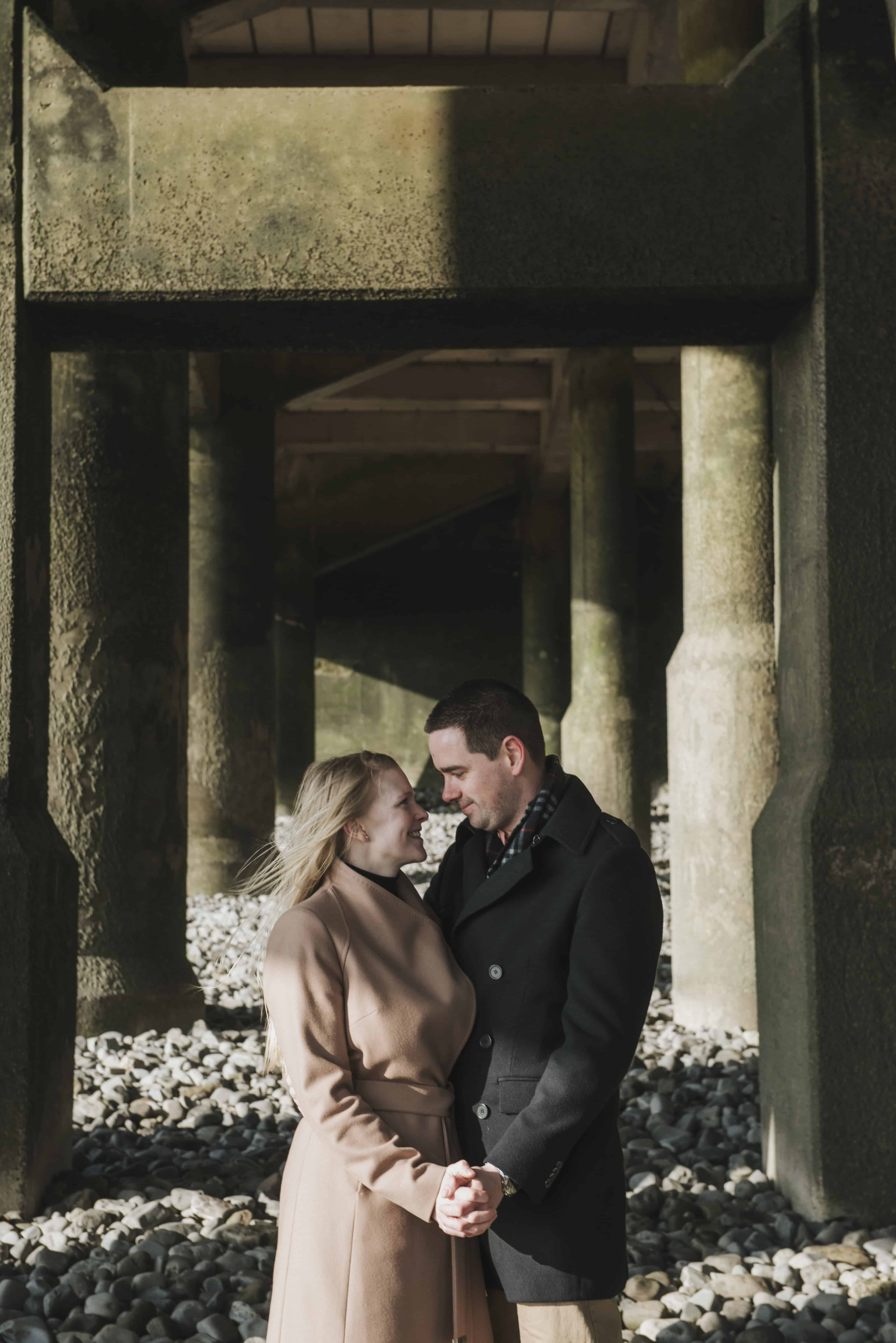 Couple stood under pier looking at each other
