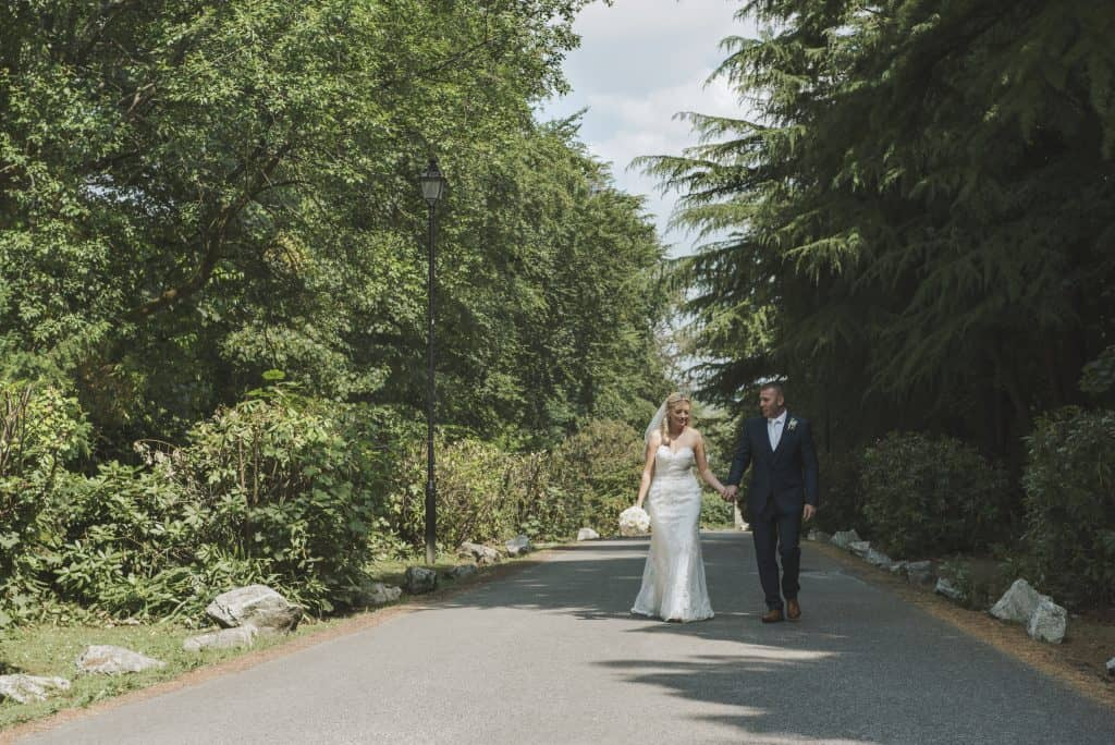 Maes Manor Hotel Wedding ~ Bride & Groom walking down a tree lined drive way