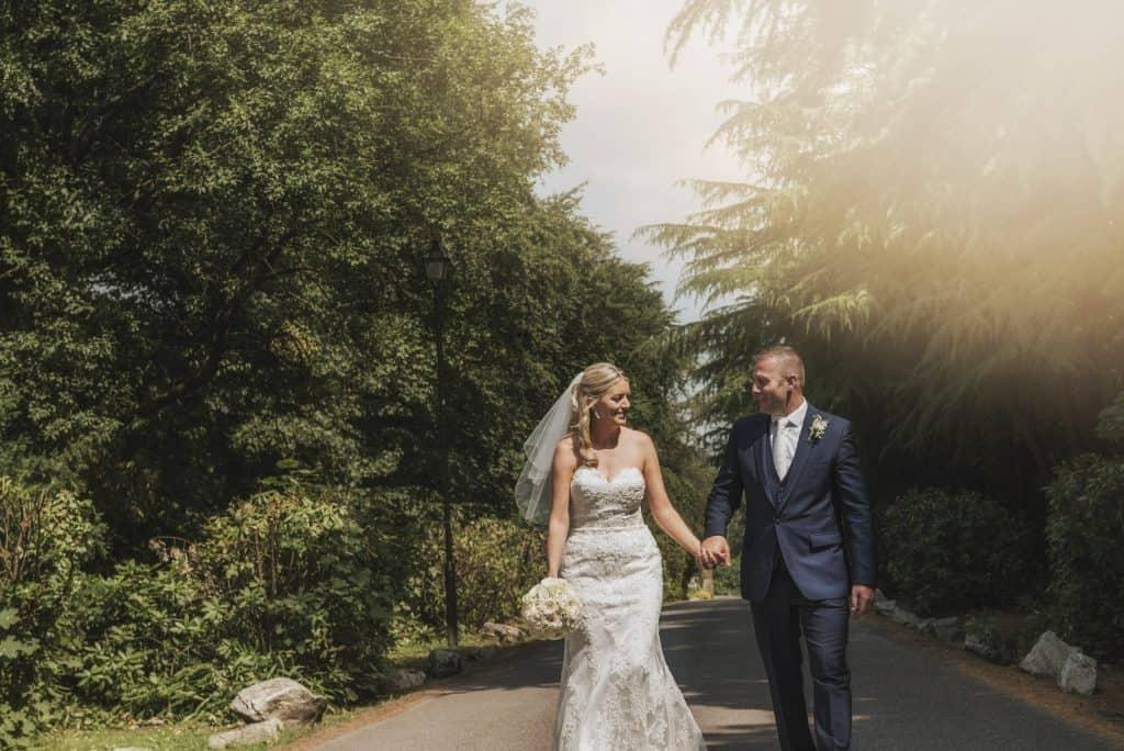 wedding photographers near me ~ Bride & Groom walking down tree lined drive way
