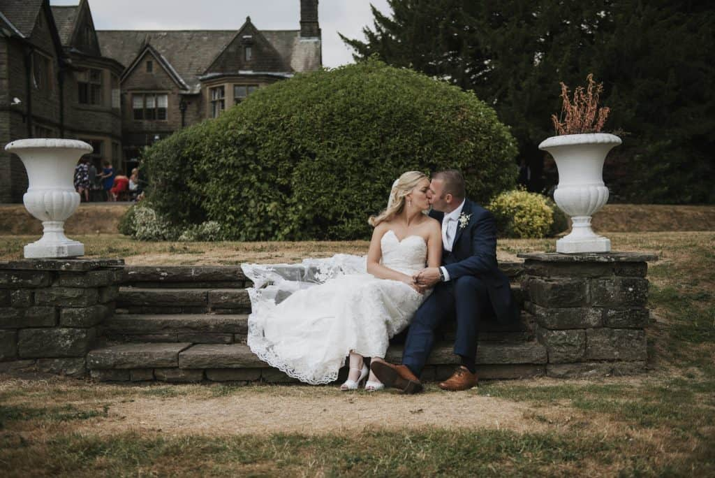 Maes Manor Hotel Wedding ~ Bride & Groom kissing sat down on steps